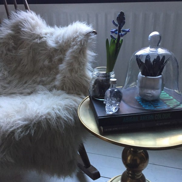 living room chair with fur throw, sidetable and ornaments