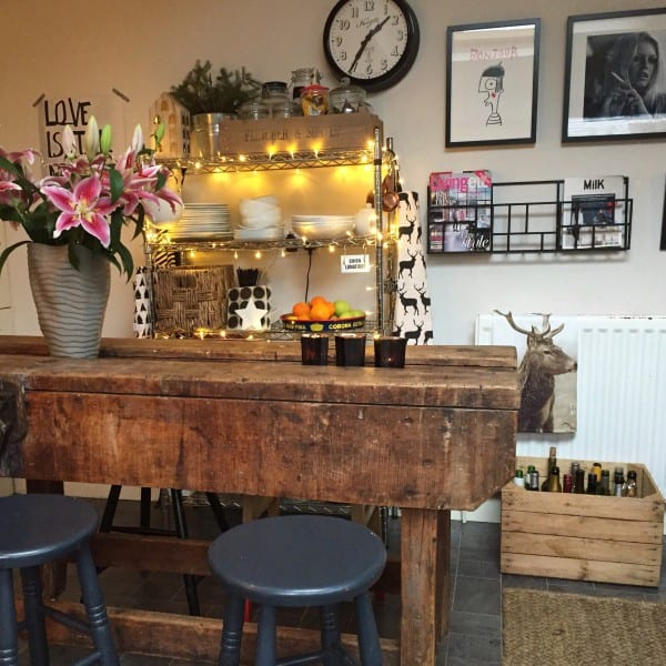wooden breakfast bar with metal shelving and fairy lighting