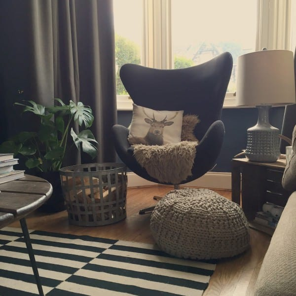 living room chair with cheeseplant and knitted pouffe